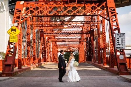 An image of a bride crossing the street of an orange industrial looking bridge holding her groom's hand and looking over her shoulder smiling at him while holding her white bouquet in the other hand.