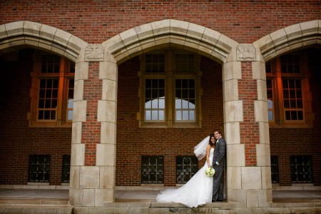 An image of a bride in her strapless white gown with her white veil blowing in the wind leaning into her groom in a dark grey tuxedo who is standing against a brick and stone pillar of the middle archway set in front of a building at the John Carroll University.