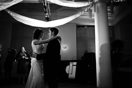 A black and white photo of a bride and groom backlit while slowing dance on the ballroom floor near a pillar at the Massimo da Milano under ceiling draping light with twinkle lights.