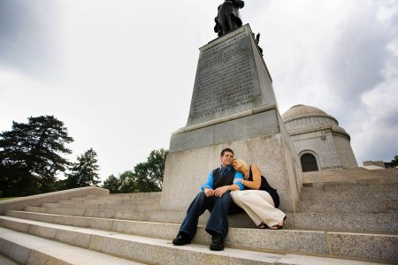 An image of an engaged couple sitting on the steps up against the statue leading up to the McKinley Monument in Canton, OH where the lady is leaning on the man's shoulder and wearing cream pants and a black top while the man is wearing a bright blue shirt, black tie, black sweater vest and jeans.