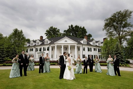 A bride and a groom stand on the green grass along with their wedding party spaced out a bit in front of the white pillared building of the Mooreland Mansion with green trees surrounding the building and grey cloudy skies above.