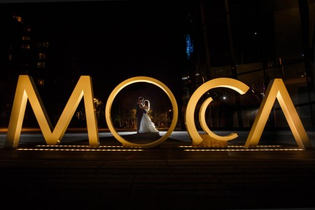 An image taken at night outside the Museum of Contemporary Art of a bride and groom embracing though the letter O of the large gold letters MOCA in downtown Cleveland, Ohio.