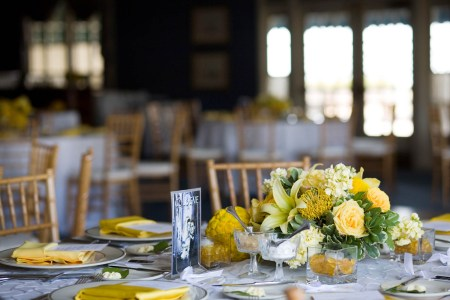 An picture of a room at the Oakwood Country Club decorated for a wedding reception with gold chairs and round tables set with white tablecloths and yellow linens as well as yellow and green floral arrangements where the table in the lower half of the photo is in focus and the rest of the room behind it is out of focus.