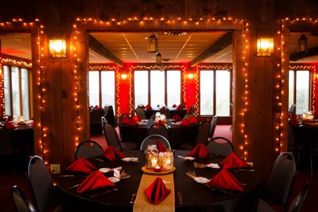 A room at the Patterson Fruit Farm is decorated for a wedding reception with round tables in black linen and red satin napkins with a burlap table runner and round wooden planks as centerpieces with mason jars full of candles while the wooden walls entryways and windows frames are all lined with white twinkle lights.