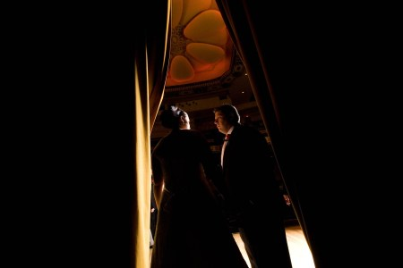 An image of a bride and groom standing face to face in the middle of the photo in the doorway of a darkened auditorium with their faces lit up and the image dark on either side of them at the Powers Auditorium.