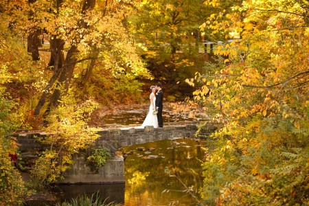 A bride leans into her groom while turning her head towards the camera as they stand right in the middle of the picture which was taken outside on a fall day in Shaker Heights, Ohio standing on a stone path with a river running right through thick trees with leaves that have started changing from green to yellow and orange.
