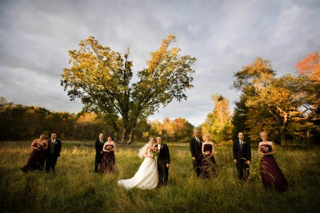 A fall outdoor image of a bride and groom standing in a grassy field under the historic Indian Signal Tree in Akron, Ohio with the bridesmaids wearing dark maroon gowns and the men wearing black tuxedos.