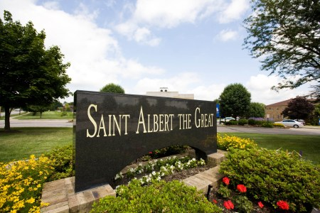 An image of a dark marble rectangular sign positioned in the middle of the photo with white lettering reading Saint Albert The Great set in the middle of a flower bed with green shrubs, and yellow, red, and white flowers in the middle of a green grassy lawn.
