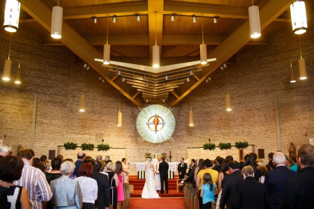 An image of a bride and groom standing at the altar in the center bottom portion of the photo before the priest at St. Basil the Great while the guests stand watching on the orange carpet and the middle to upper half of the photo shows the creamed colored brick walls with an unusual piece of artwork shaped in a white sunburst pattern with a painted image of Jesus standing in front of a cross in the middle of it and large wooden beams fill the top portion of the photo.