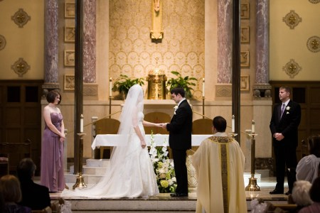 An image of a bride and groom standing in the middle center of the photo facing each other at the altar where the bride has her left arm outstretched and the groom is placing the ring on her finger and the maid of honor stands in purple to the left while the best man in his black tuxedo and purple tie is standing to the right and the priest is standing with his back to the camera in the lower left of the photo and the upper half of the photo shows the cream colored back wall with a geometric pattern and purple marble pillars inside St. Charles Borromeo.