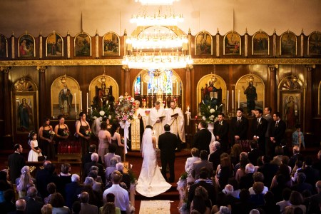 A bird's eye view of a bride and groom standing at the altar of the ornate St. Haralambos church where the carpet is deep red and the walls are ordained with holy painted images surrounded in ornate gold frames and the wedding guests are seated under a bright chandelier.