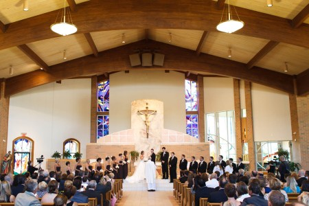 A photo taken inside the bright sanctuary of St. John Vianney church facing down the center aisle where the priest is standing at the altar with his back to the camera and a bride and groom are behind him facing him and the wedding party is lined up on either side the couple while the guests sit in the pews on either side watching and the background has a back cream colored wall with an arched wooden pillar lining the top of the photo and a large ceramic crucifix is attached to the wall with purple stained glass windows on either side.