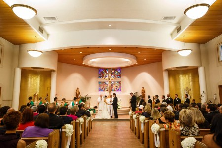 A picture of a bride and groom holding hands on the altar while the guests in the pews look on at St. Michael the Archangel church which has gold glittered walls in the corners, a square stained glass window at the back of the altar with Christ on the cross in front of it.