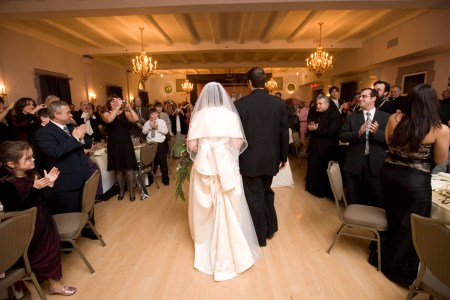 An image from behind of a bride and groom entering the reception hall walking hand in hand in the center of the wedding guests standing at the tables clapping at the Metropolitan Centre.