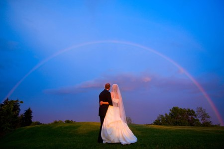 A stunning shot of behind a bride and groom standing side by side with their arms around each other waists on a grassy hill looking out at a rainbow arching right over them on an extremely blue sky at dusk.