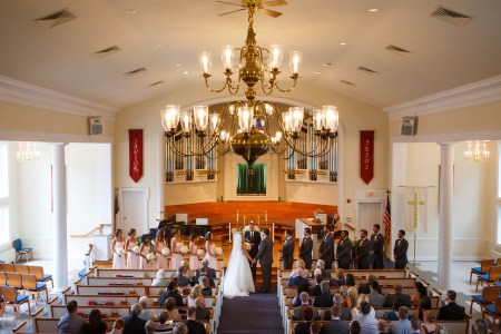 A bride and groom stand holding hands at the altar inside the bright sanctuary of the Church of the Lakes with bridesmaids in pink gowns with white and pink bouquets and groomsmen in dark grey tuxedos and a chandelier at the top of the picture.
