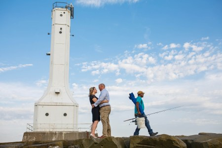 An image of an engaged couple where the woman is in a black dress with white high heels facing the man while they are hugging and he is wearing tan pants and a blue button down shirt standing at the bottom of the photo on large boulders with an old white light house to the left of the couple and a fisherman walking away from the couple on the right carrying a white bucket, a fishing pole, and a blue camping chair slung over his arm all under a blue sky with white puffy clouds in Huron, Ohio.