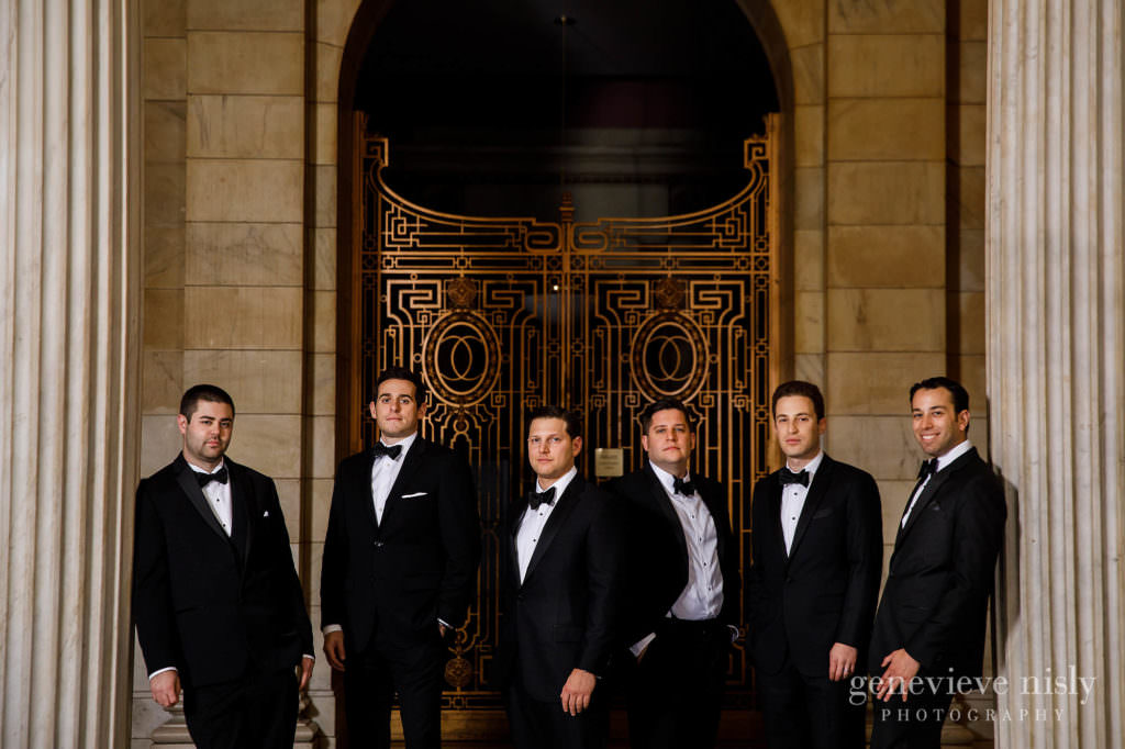 Groomsmen in front of an iron grated door.
