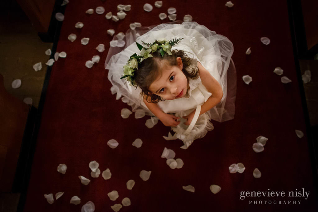 Flower girls looks up while playing with flower pedals during the wedding ceremony.