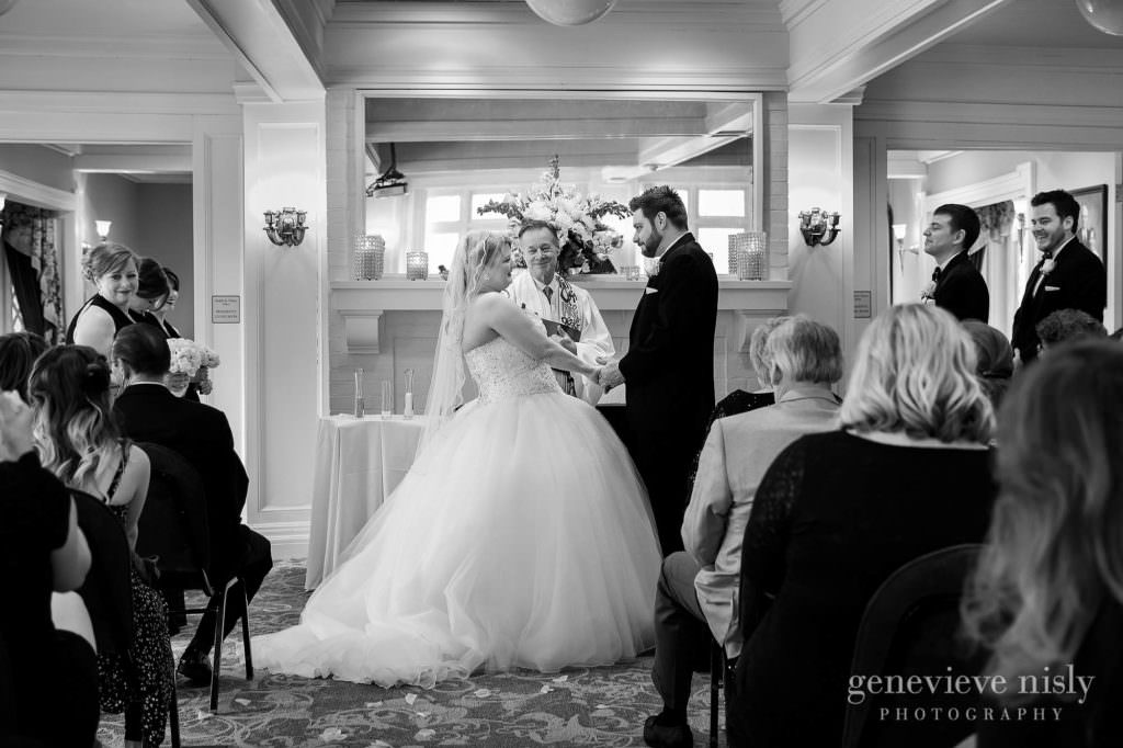 The bride and groom hold hands during their ceremony at Mooreland Mansion in Kirkland.