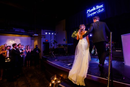 An image taken in a darkened room at the Music Box Supper Club where a bride and groom are stepping up together onto the stage in the right side of the photo under purple and blue lights and guests are standing and clapping for them on the right side of the photo.