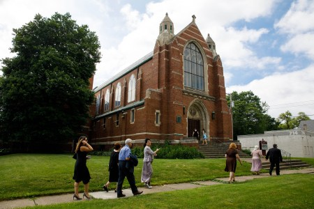 An image of the outside of the Concordia Lutheran Church where a handful of wedding guests are walking on the sidewalk leading up to the brick building.