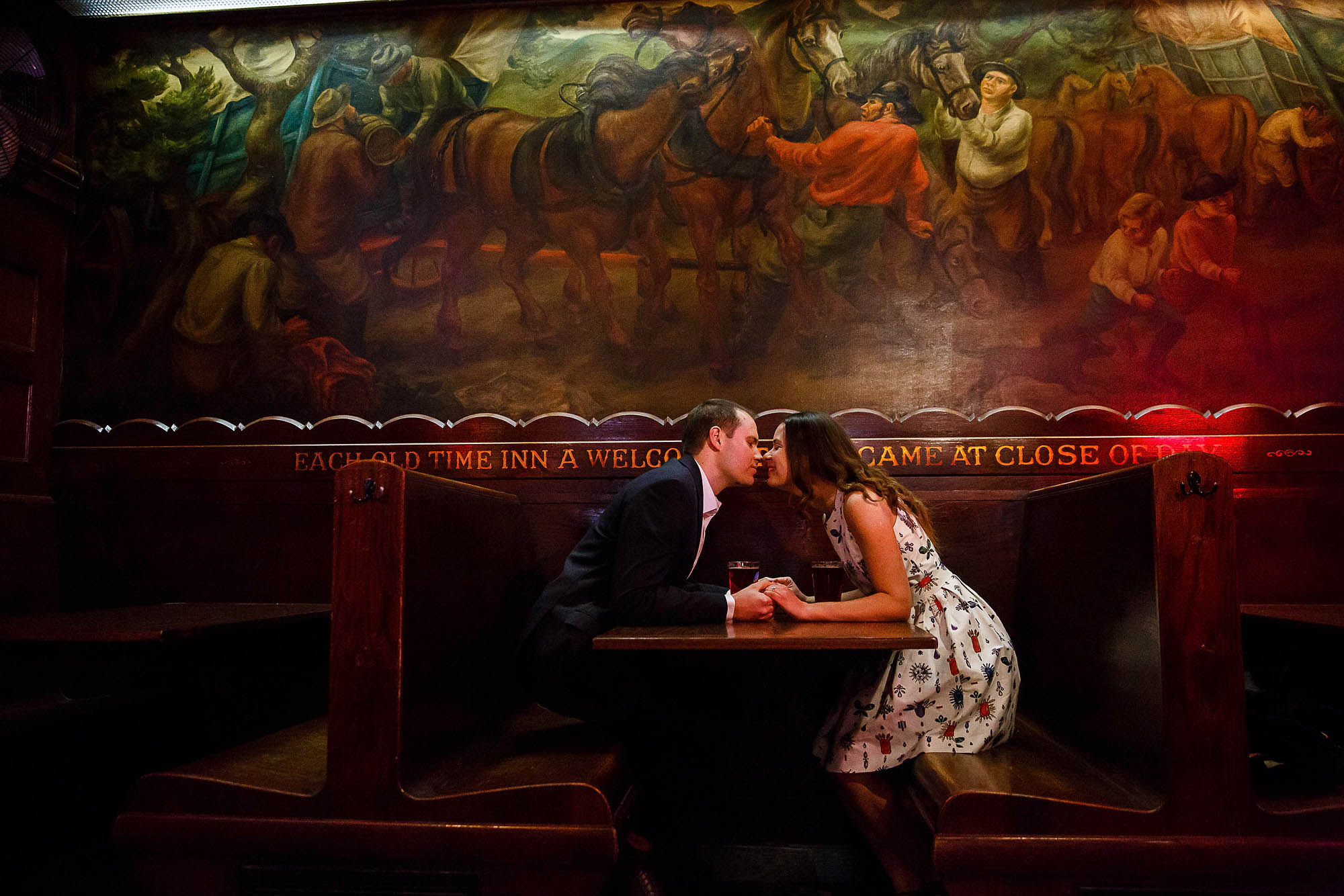 An engaged couple in a dress and suit coat with a tie are sitting in a dark booth holding hands and leaning in for a kiss with a painted mural of a horse scene on the wall behind them taken in Canton, Ohio.
