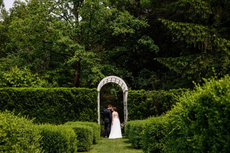 Bride and groom kiss under an archway at Fellows Riverside Gardens in Youngstown, Ohio.