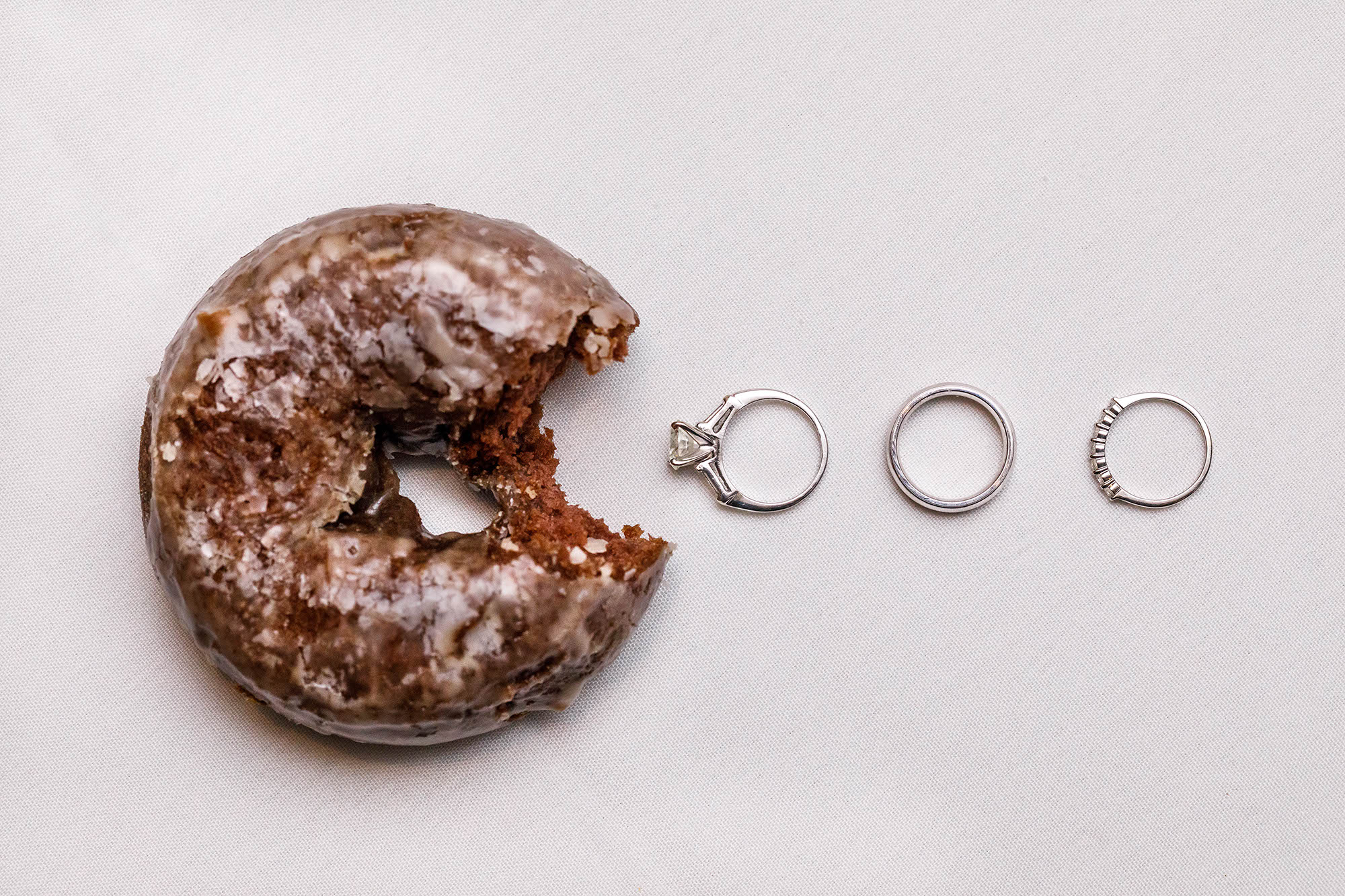 "A chocolate donut from Bakers ""eats"" an engagement ring and wedding band set pac-man style."