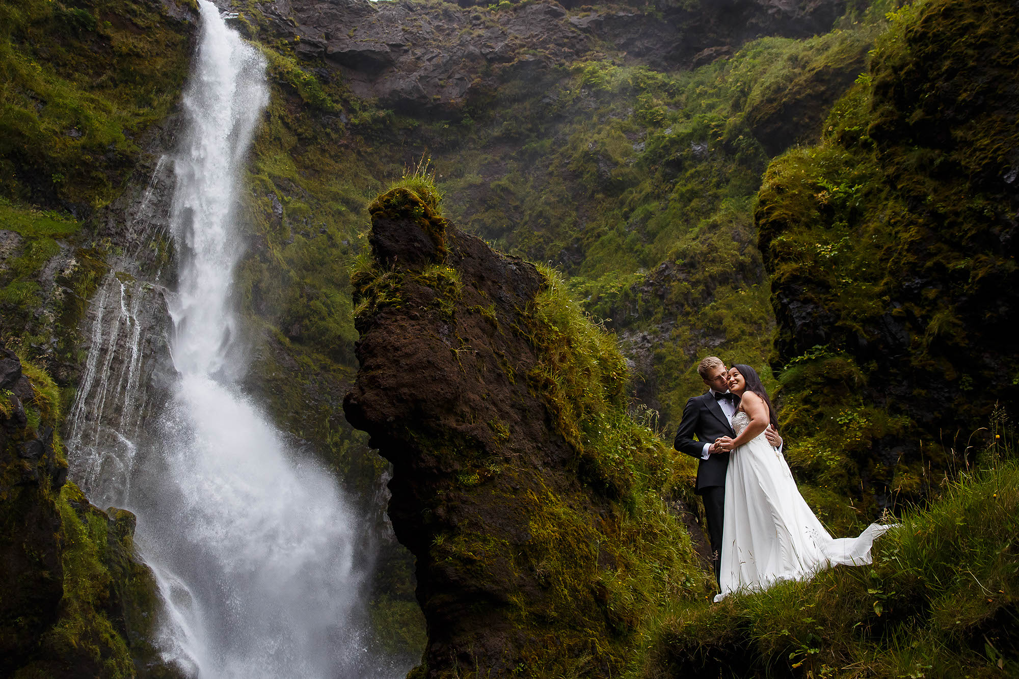 An elopement to the South Region of Iceland for their wedding and stopped at the waterfall Seljalandsfoss in the middle of lush green and rocky landscape with the white falls in the background.