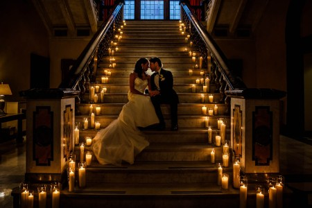 Bride and groom take a moment on candle lit steps of The Union Club in Cleveland during their wedding.