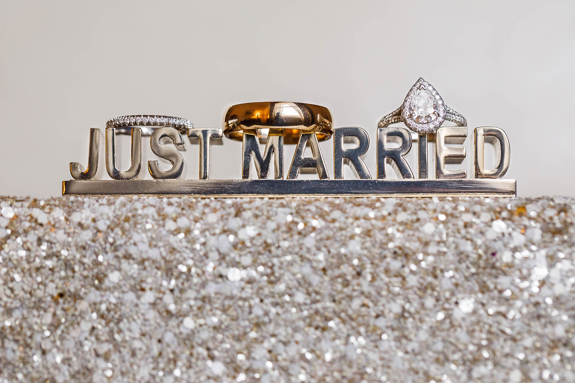 "Wedding and engagement rings on top of a sparkly ""Just Married"" clutch at the Union Club Downtown Cleveland, Ohio."