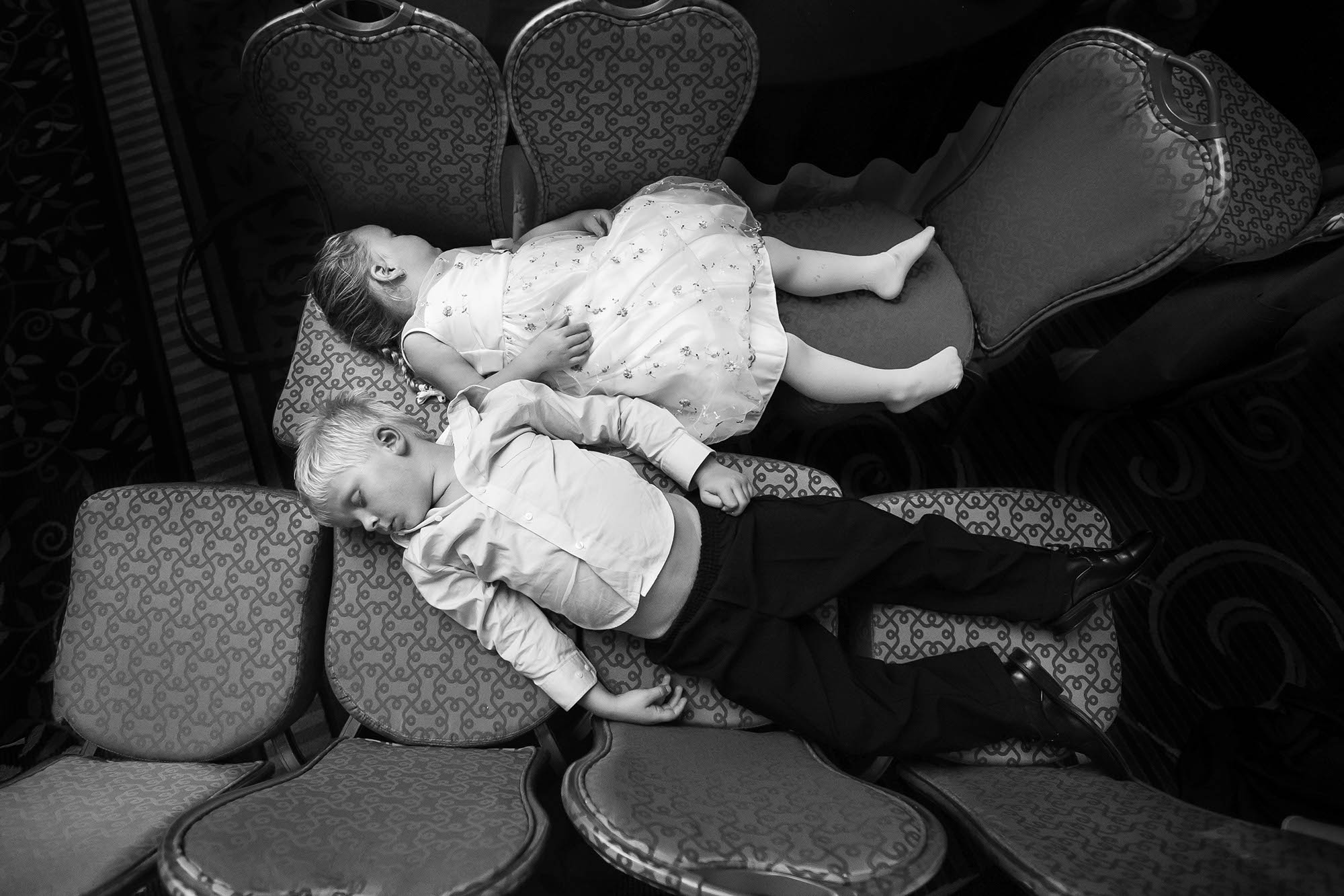 A precious candid moment captured of an exhausted flower girl and ring bearer who both fell asleep on during the wedding reception at the Marriott in downtown Cleveland, Ohio.