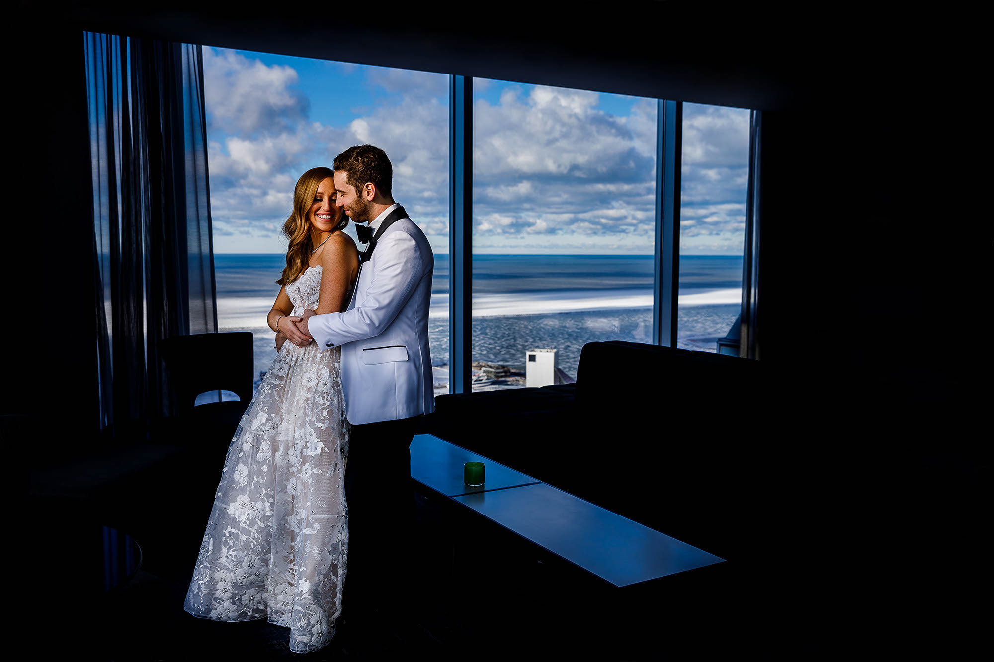 A sunlit bride and groom on a cold winter day at the top floor of The Hilton Cleveland Downtown Hotel.