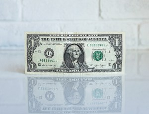 A one dollar bill standing against a brick wall with its reflection showing on the table below it
