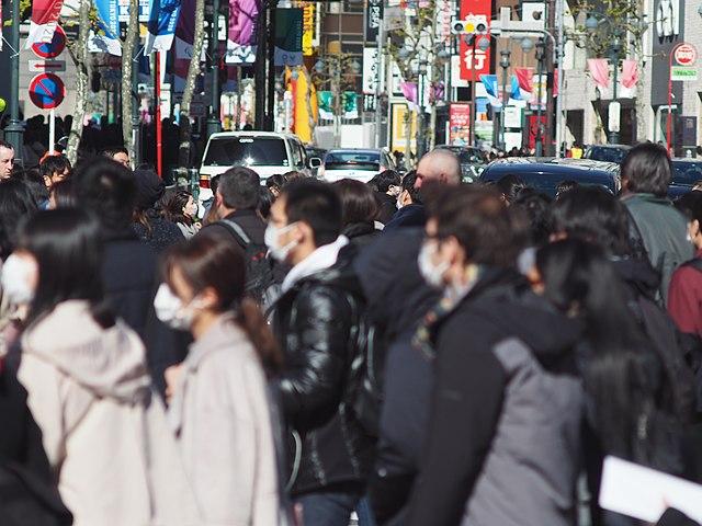 pessoas usando máscaras andando em Shibuya