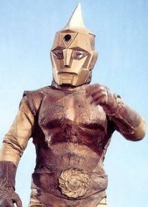 Uma personagem fictícia. Um homem com aparência de robô de cores dourada e bronze.