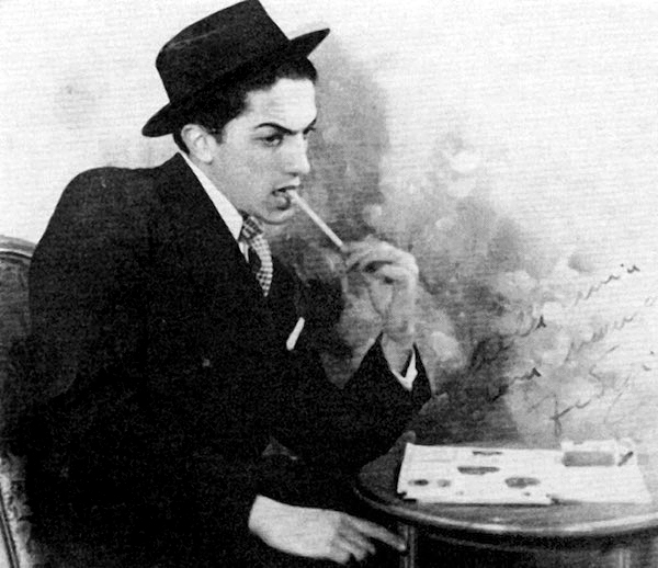 Federico Fellini ritratto mentre riflette on la penna in bocca, aspirante scrittore