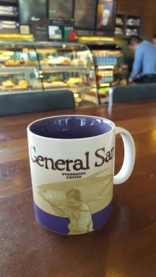 THE ICONIC MAN CARRYING A GIANT TUNA ON HIS SHOULDERS ADORN THE FRONT PORTION OF THE GENSAN STARBUCKS MUG