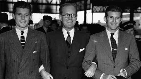 JFK with father and brother wearing adark on light chalk stripe with striped knit tie and collar pin