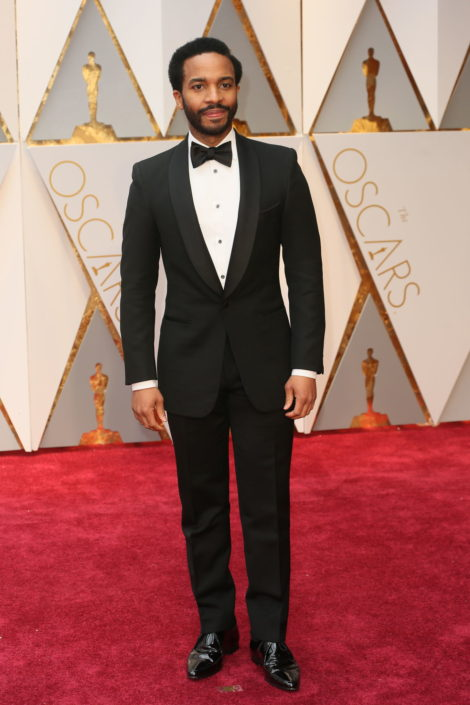 André Holland in a proper slim shawl collar Tuxedo with shirt studs, self tie bow tie, cummerbund and patent leather Derby Shoes