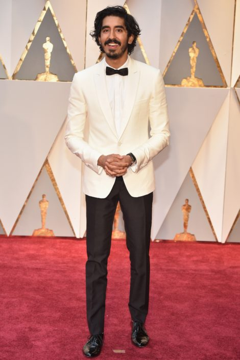 Dev Patel with off white Dinner Jacket, hidden fly shirt and slim bow tie with patent leather shoes