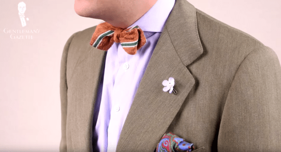 A green suit combined with a pastel colored dress shirt with an orange shantung bow tie