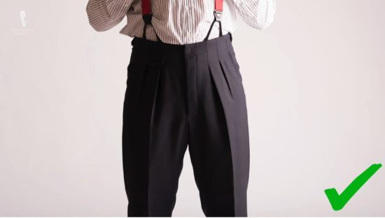 Navy pants with inward pleats worn with suspenders for a smooth look