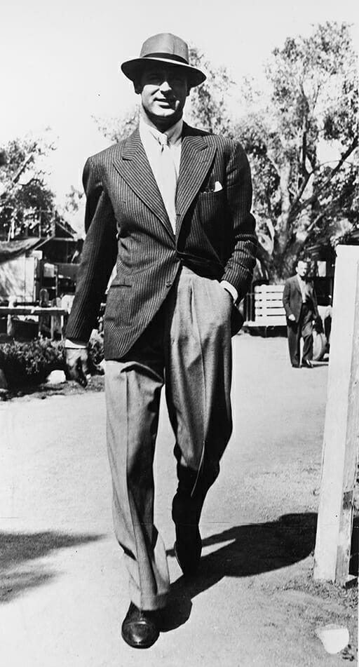 British born actor Cary Grant (1904 - 1986) walking outdoors wearing a pinstripe jacket and a hat, 1940s.