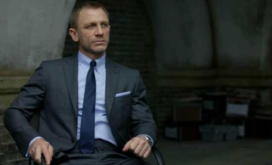 Daniel Craig as James Bond in a mid-gray suit with mid-blue tie.