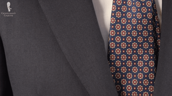 A dark suit with Fort Belvedere micropattern tie