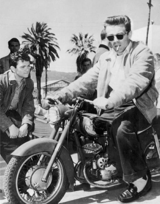 James Dean astride a motorcycle.