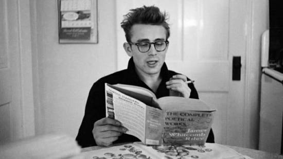 Dean wears a pair of tortoise-shell eyeglasses to read a book of poetry.