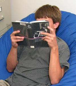 Picture of a boy reading a Mark Twain book